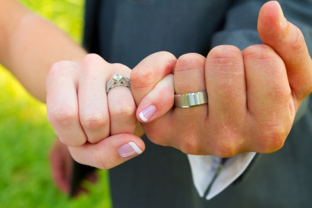 Bride and groom with their hands together and their pinky fingers interlocked for this unique color image of their hands and wedding rings.