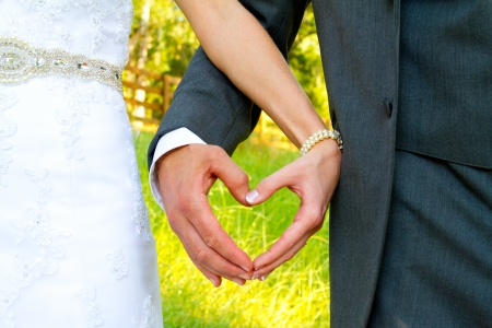 Heart shape is formed by the bride and groom putting their hands together while standing outside in a country field on their wedding day.