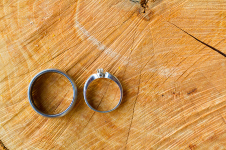 Two wedding rings together at a winery in Oregon, the rings are placed on a piece of wood. Stock Photo