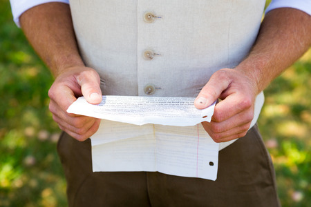 wedding vows: Handsome groom reading his vows for practice before the wedding ceremony. Stock Photo