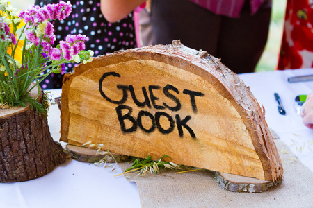 crosscut: Guestbook sign is made from a crosscut section of a fir tree with the letters guest book burned into the wood grain at a wedding ceremony.
