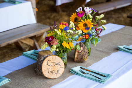 Wedding decor and decorations are made up of wildflowers and crosscut sections of fir trees at this organic natural reception in Oregon. photo
