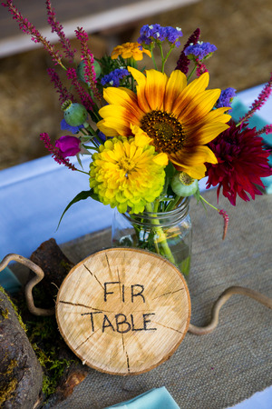 wedding decor: Wedding decor and decorations are made up of wildflowers and crosscut sections of fir trees at this organic natural reception in Oregon.