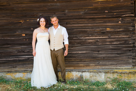 relational: Copyspace on a wood texture wall with the bride and groom sharing a moment on their wedding day. Stock Photo