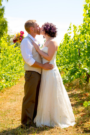 Bride and groom sharing a moment and posing for the camera in this portrait of the two people in a vineyard at a winery on their wedding day. Reklamní fotografie