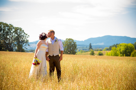 getting married: Natural meadow or field plays host for this portrait of the bride and groom on their wedding day after just getting married during their ceremony.