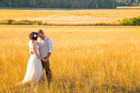 Wedding couple shares a romantic moment in a field or meadow at sunset on their wedding day. photo