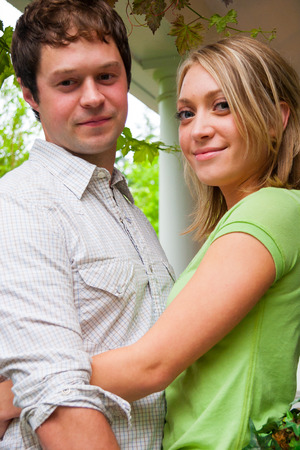 Engaged couple pose for a portrait during their engagement photos while standing on a white country porch.