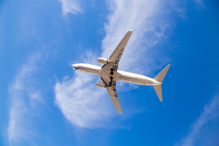 Airplane flying overhead with blue sky and the bottom of the airplane as it comes in for a landing at San Diego Airport. Stock Photo