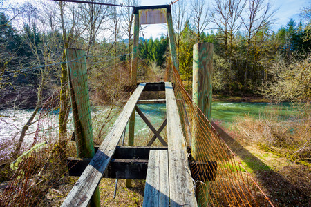 Very old swinging bridge crosses the Siuslaw River near Mapleton Oregon. This bridge was used to access a farm on the other side of the river but is no longer in use. Stock Photo