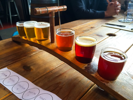 Craft beers are served together in a sampler tray for the beer enthusiast at a restaurant in Oregon. Publikacyjne