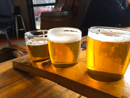 sampler: Craft beers are served together in a sampler tray for the beer enthusiast at a restaurant in Oregon. Stock Photo