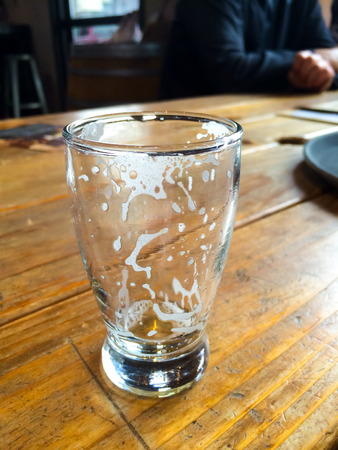 resides: Foam head resides in this empty beer glass after it has been drunk at a restaurant. Stock Photo
