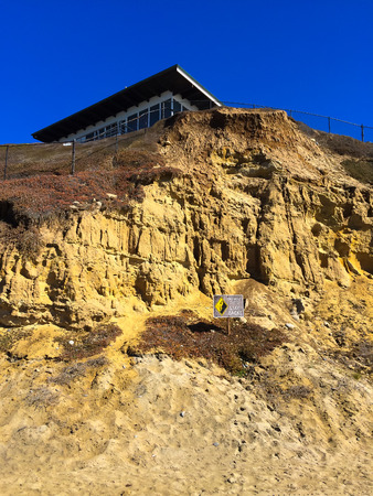 deemed: California cliffs are deemed unstable and there is a danger sign warning of the issue with a house above at this beach. Stock Photo