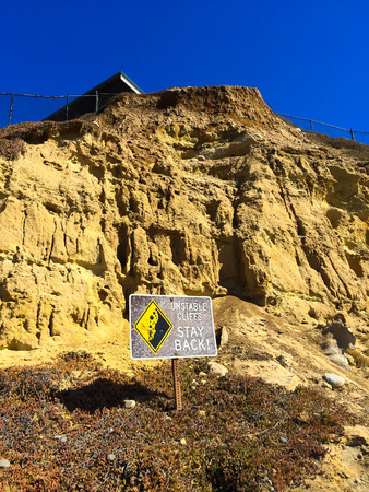 California cliffs are deemed unstable and there is a danger sign warning of the issue with a house above at this beach. Imagens