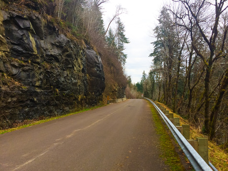 An old mountain road cruising through the forest of rural Oregon. Stock Photo