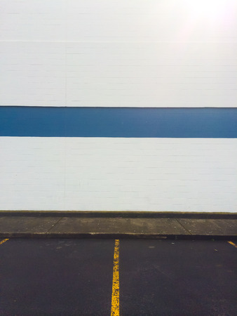 White wall with a blue stipe and a yellow line in the parking lot create this unique abstract background. photo