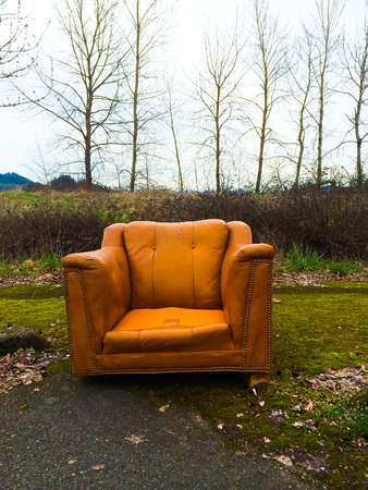 worthless: Urban decay and an abandoned orange chair next to some winter trees.