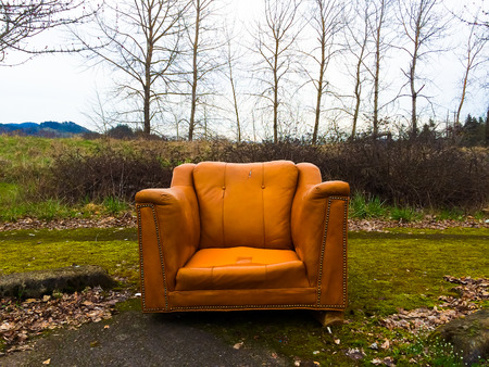 Urban decay and an abandoned orange chair next to some winter trees.