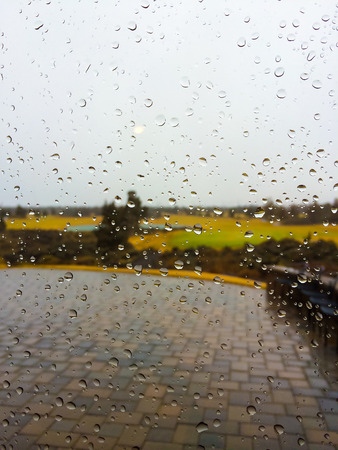 inclement: Rain drops on a glass window with very inclement winter weather outside.