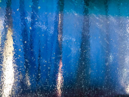 Photo from inside a car as it goes through a car wash and the windshield of the automobile is cleaned.