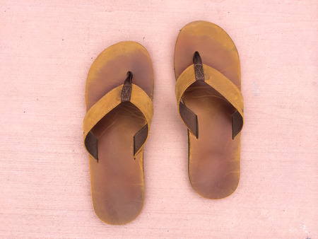 Sandals with no feet on the ground that are quite worn and old but in good condition for this type of leather footwear. photo