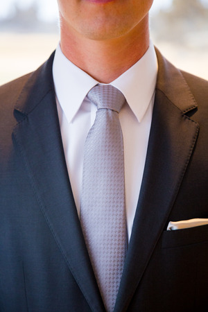 Groom wearing a necktie on his wedding day with a classy fashionable suit and tie. Imagens