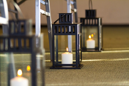 decor: Wedding decor in the aisle at a ceremony using candles in lanterns set on the floor.