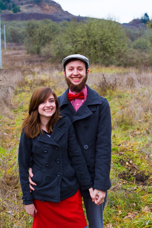 Portrait of a happy couple engaged to be married in the winter outdoors. This couple is modern, trendy, hipster, and fashion first.