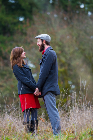 Engaged and in love, this couple poses for portraits outdoors in the winter.