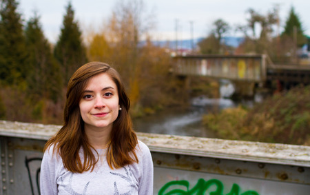 Girl on a bridge with an out of focus background for this hipster, trendy fashion portrait. Banco de Imagens
