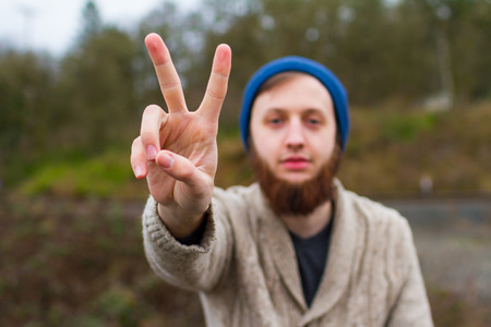 two persons only: Hippie man sitting on a bridge giving a peace sign in this trendy hipster fashion portrait. Stock Photo