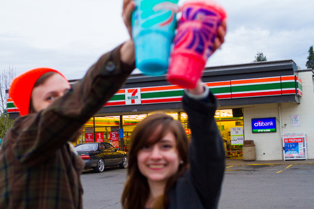 Springfield, Oregon, USA - January 6, 2014: Engaged couple holding slurpees in front of 7 Eleven celebrating their engagement.