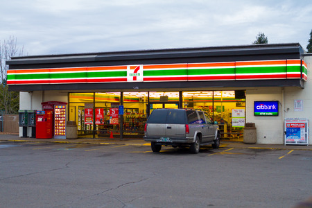 store: Springfield, Oregon, USA - January 6, 2014: 7 Eleven convenience store at dusk with lights on and an suv parked out front.