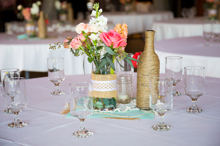 wedding reception decoration: DIY wedding decor table centerpieces with wine bottles wrapped in burlap twine and rose flowers. Stock Photo