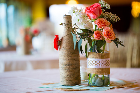 wedding table decor: DIY wedding decor table centerpieces with wine bottles wrapped in burlap twine and rose flowers. Stock Photo