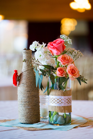 DIY wedding decor table centerpieces with wine bottles wrapped in burlap twine and rose flowers. Standard-Bild