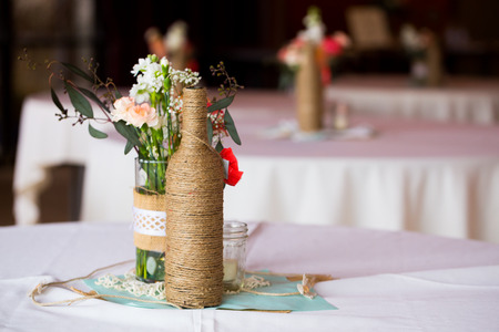 decor: DIY wedding decor table centerpieces with wine bottles wrapped in burlap twine and rose flowers. Stock Photo