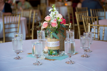 wedding decor: DIY wedding decor table centerpieces with wine bottles wrapped in burlap twine and rose flowers. Stock Photo