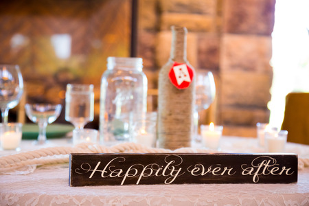 Wedding decor sign that says happily ever after with reception details blurred out of focus in the background. Stock Photo