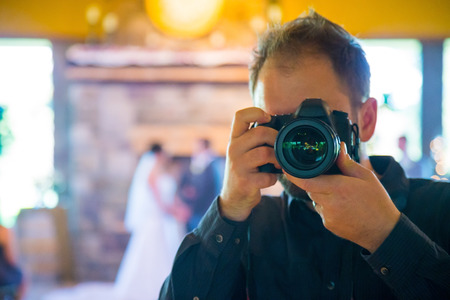 Wedding photographer with a DSLR and professional lens shooting photos of the bride and groom during the ceremony, self portrait. Stock Photo