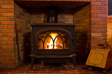 Fire burning in a wood stove at a lodge cabin. Stock Photo