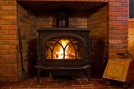 estufa: Fuego que quema en una estufa de leña en una cabaña de refugio. Foto de archivo