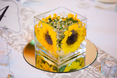 Flowers in glass on the tables for the centerpieces at this indoor wedding reception. photo