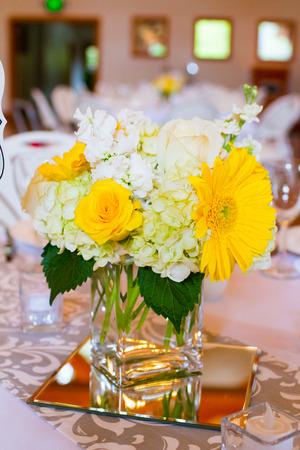 Bloemen in glas op de tafels van de blikvangers in deze indoor bruiloft receptie.