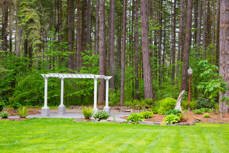 Outdoor wedding ceremony venue with white pergola set against some Oregon trees. Stock Photo - 28208423