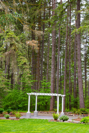 venue: Outdoor wedding ceremony venue with white pergola set against some Oregon trees.