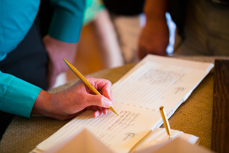 Person Signing The Guestbook At A Wedding Ceremony And Reception Stock Photo