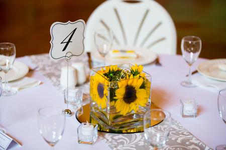 이 실내 결혼식 피로연에서 중앙 장식품을위한 테이블에 유리로 된 꽃.