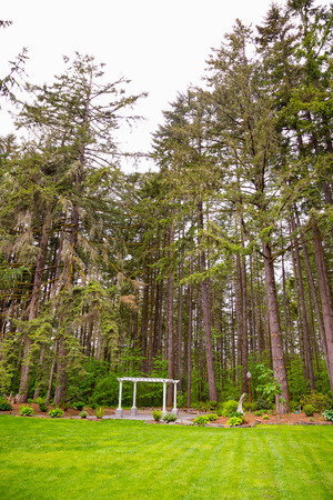 Outdoor wedding ceremony venue with white pergola set against some Oregon trees. Stock Photo - 28208638